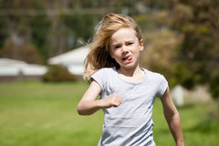Child running. A little blond girl running cross country in a race Royalty Free Stock Photos