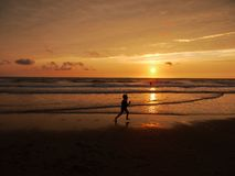 Child running across beach at sunset. A child running joyously through the surf on a cornish beach at sunset Stock Image