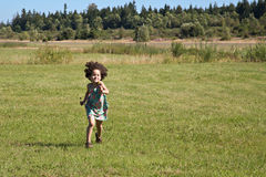 Child running across field Stock Image
