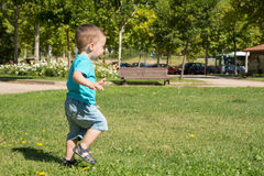 Child running. Across the lawn of a park Royalty Free Stock Photo