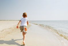 Child running along beach. Young boy running along beach by sea, seen from behind Royalty Free Stock Photos