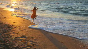 Child running along the surf. At sunset. Slow motion stock video