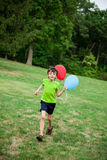 Child running with balloons Stock Image