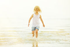 Child running beach shore splashing water Stock Images