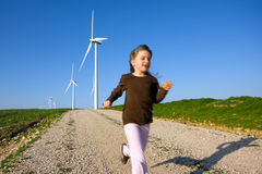 Child Running. blue skies and windmills. Child running down dirt road. Wind turbines in background. Blue sky and green grass flanking road Stock Photography