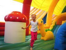 Child running in bouncy castle. Child running in color bouncy castle outdoor Stock Images