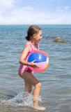 Child running with a colorful ball Stock Photos