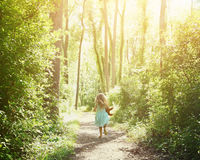 Child Running Down Secret Nature Trail. A little child is running down a nature trail with sunlight on the trees for a happiness or freedom concept stock photos