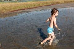 Child running in healing mud Stock Photography
