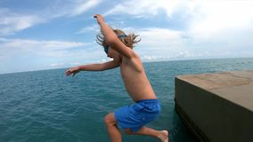 Child running and jumping off pier in sea water.