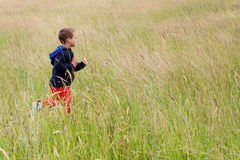 Child running on meadow Stock Images