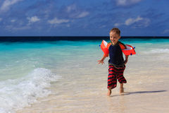 Child running on sand beach Stock Photo