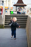 Child running with toy windmill Royalty Free Stock Images