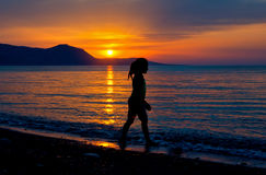 Child running on water at sea beach sunset. Royalty Free Stock Images