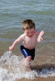Child running through water Royalty Free Stock Photos