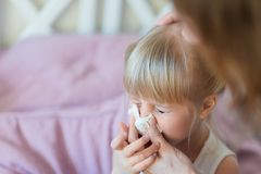 Child with runny nose. Mother helping to blow kid`s nose with paper tissue. Seasonal sickness.  Stock Image