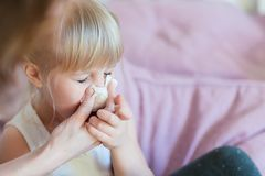 Child with runny nose. Mother helping to blow kid`s nose with paper tissue. Seasonal sickness royalty free stock image