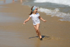 Child runs along the beach Stock Image