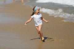 Child runs along the beach Stock Image