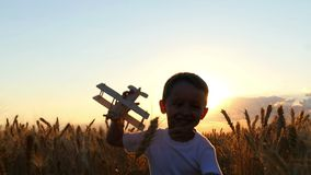 A child runs along the wheat field during sunset, holding a toy plane in his hands. The boy shows the flight of the
