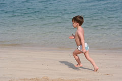 The child runs on a beach Stock Images
