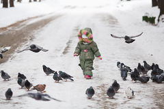 Child runs through a flock of pigeons on the square in winter city park Stock Photos