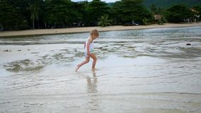 The child runs gleefully along the beach, creating a spray of water. The child runs gleefully along the beach, creating a spray stock video footage