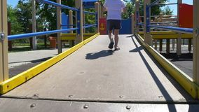 The child runs through the playground in a slow motion. Slow motion stock video