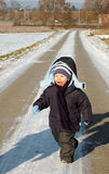 Child runs on the road. Child runs on the road in winter Royalty Free Stock Photos
