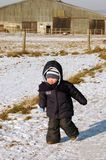 Child runs on the road. Child runs through snow-covered road Royalty Free Stock Photo