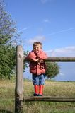 Child in a Rural Landscape. A child on a fence stock image