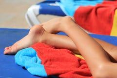 年轻child& x27; s腿和明亮的色的毛巾在太阳懒人在阳光下 免版税库存照片
