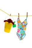 Child's bathing suit and toys on clothes line. Isolated child's bathing suit and toys on clothes line with white background Stock Photo