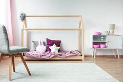 Child`s bed in bright interior. Grey chair in front of child`s bed with satin bedding next to white cupboard in bright interior Stock Photography
