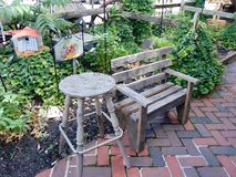 Child`s Bench & Stool. A child`s bench and stool set on the brick sidewalk in front of a garden royalty free stock photo