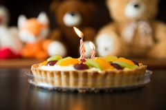 Child`s Birthday cake with candles, soft toys as background stock photography