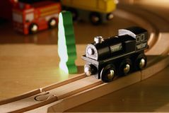 Child's black wooden toy train on wood tracks