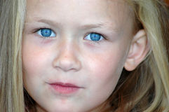 Little girl child blue eyes. A beautiful little caucasian white girl child head portrait with bright blue eyes, long blond hair and smiling expression in her Stock Photos
