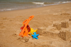 Child's bucket, spade and other toys on tropical beach Royalty Free Stock Image