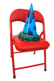 Child's chair with party hat. Isolated on white Royalty Free Stock Photo