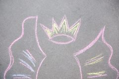 Child`s chalk drawing of crown and wings. On asphalt, top view stock image