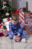 Child's Christmas. Child opening presents near the Christmas tree, Holiday has finally arrived Royalty Free Stock Photography