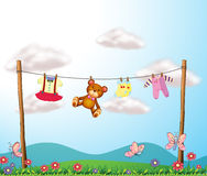A child's clothes hanging with a teddy bear Royalty Free Stock Images