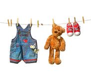 Child's clothes with teddy bear on clothesline. On white stock photography