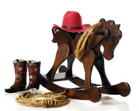 A Child's Cowboy Gear. The gear necessary to play cowboy:  A pair of boots, a gun, rope, hat and a wooden rocking horse.  Isolated on white Stock Photography