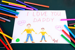 Child's drawing Daddy, I love you closeup. Child's drawing Daddy, I love you and a lot of colored pencils and markers on the table Royalty Free Stock Photos