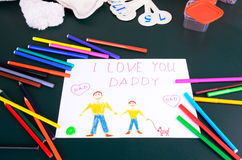 Child's drawing Daddy, I love you. And a lot of colored pencils, markers and toy on the green table Royalty Free Stock Image
