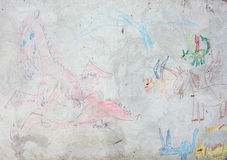 Child's drawing of a dragon. On a cement wall royalty free stock image