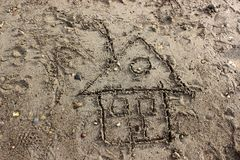 Child's Drawing of a House in Sand. A child-like drawing of a house in the sand at the beach Royalty Free Stock Images