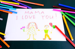 Child's drawing Mama, I love you closeup. Child's drawing Mama, I love you and a lot of colored pencils and markers on the green table Royalty Free Stock Images